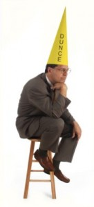 executive thinking on a stool, wearing a dunce hat on white background
